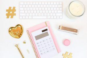 Photographie d'une calculatrice blanche sur un calepin rose permettant de calculer avec précision son taux d'engagement sur Instagram
