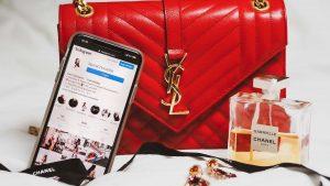 Photo d'un iPhone avec l'application Instagram ouverte où on aperçoit un beau feed de photos. Le téléphone est placé contre un sac de luxe rouge à côté d'une bouteille de parfum.